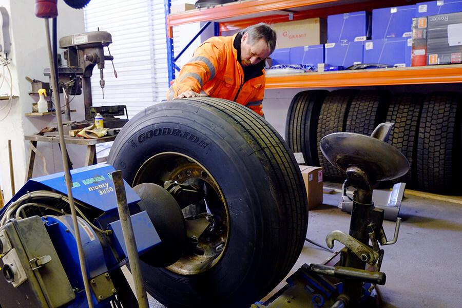 Mitarbeiter wuchtet Rad in der eigenen Werkstatt